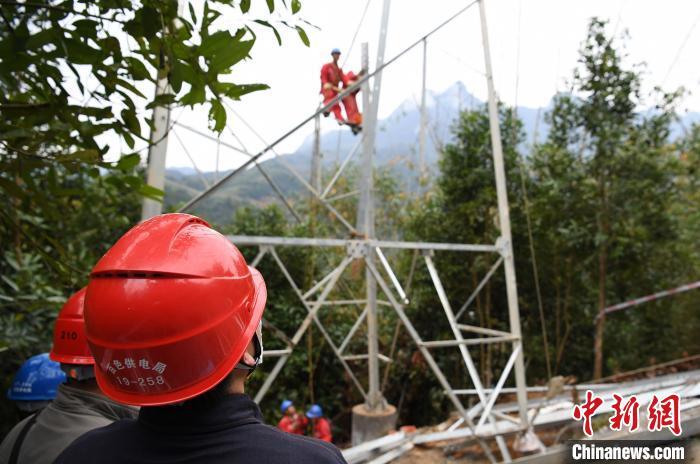 南方电网广西新电力集团那坡35千伏上盖至百合送电线路工程施工现场,施工人员做好安全防护措施,在高空紧张地开展组塔作业。 陈钦荣 摄