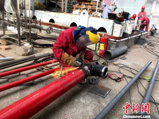 施工队正在进行管道焊接。 李佩珊 摄